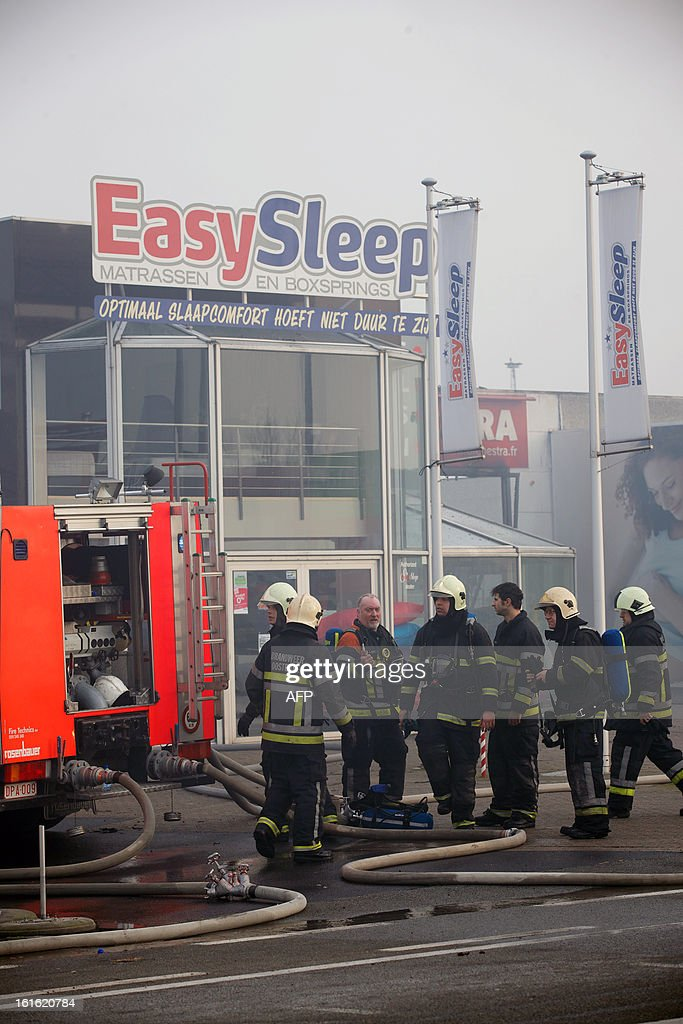 Belgian firefighters work at an industrial site in Oostende on February 13, 2013, where a fire started earlier during roofing construction works at baby specialty store Premama, and quickly spread to other buildings, without injuring any casualty, according to firefighters. AFP PHOTO / BELGA / KURT DESPLENTER