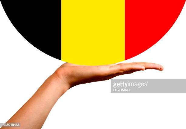 Belgian Flag in a hemisphere, on the palm of a hand.