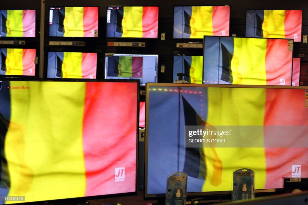 Belgian flags are broadcast a few moments before King Albert II of Belgium appears on TV screens displayed in a store in Brussels on July 3,2013, while delivering a speech from the royal palace in Brussels. Belgium's King Albert II today announced his abdication in favour of his son Philippe after two decades at the helm of the tiny country. 'I intend to abdicate on July 21,' the sovereign said in a speech broadcast to the nation from the royal palace.
