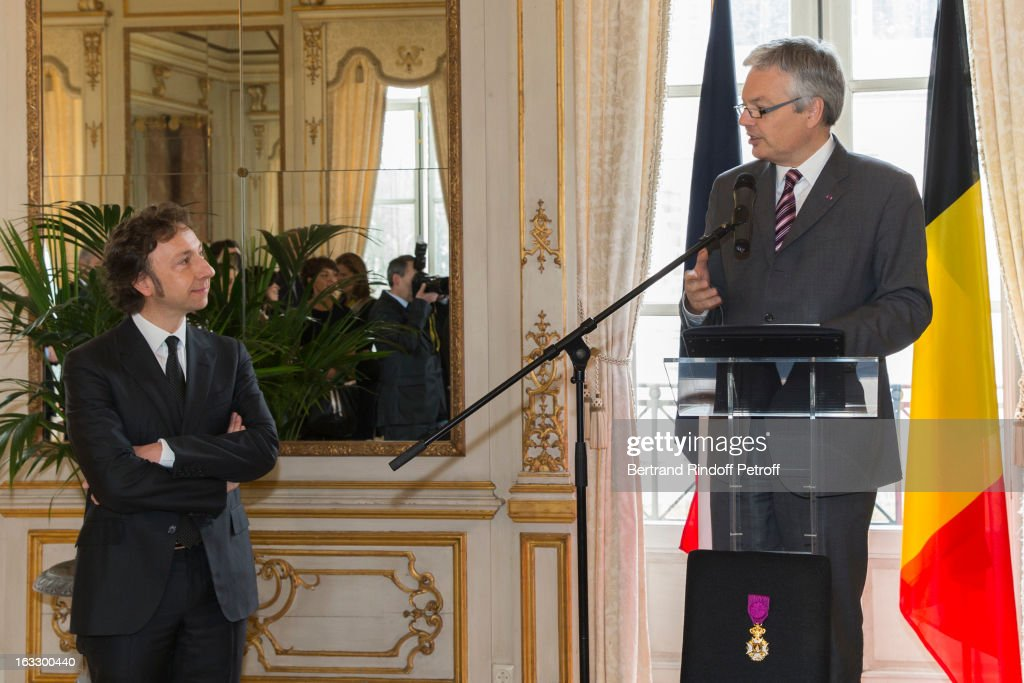 Belgian Foreign Minister and Vice Prime Minister Didier Reynders (R) delivers a speech prior to appoint French journalist and author Stephane Bern (L) officer in the King Leopold order during a ceremony at Palais d'Egmont on March 7, 2013 in Brussels, Belgium.