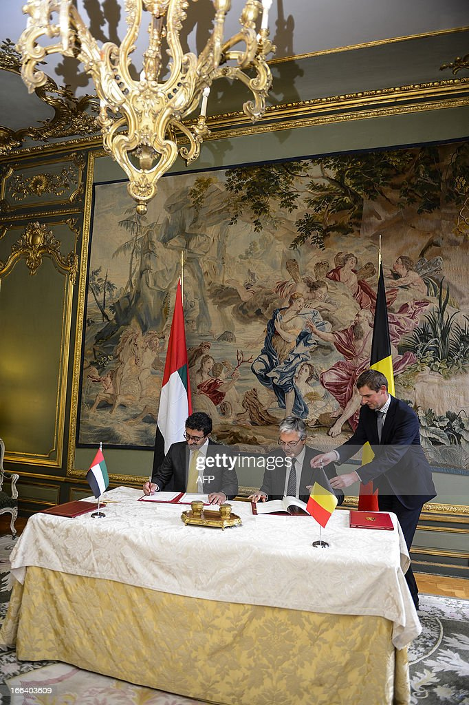 Belgian Foreign Minister Didier Reynders (C) signs documents with United Arab Emirates' Foreign Minister Sheikh Abdullah bin Zayed al-Nahyan, at the Egmont Palace in Brussels on April 12, 2013.