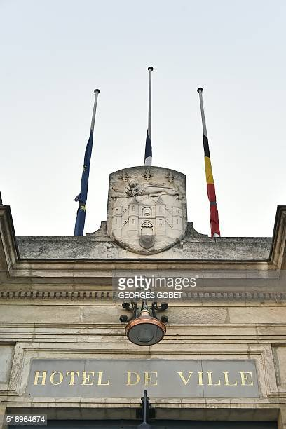 Belgian French and European flags are seen half mast at the city hall of Bordeaux on March 22 2016 in tribute to the victims following a series of...