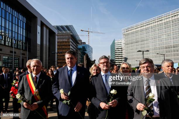 Belgian Interior Minister Jan Jambon and European Commissioner for the Security Union Julian King hold white roses during a march in support of...