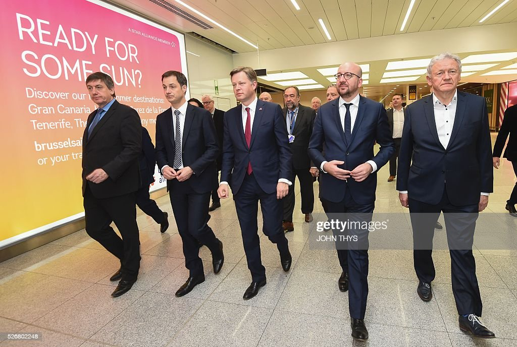 Belgian Interior Minister Jan Jambon, Telecom and Postal services Alexander De Croo, Brussels Airport CEO Arnaud Feist, Belgian Prime Minister Charles Michel and Minister of Mobility Francois Bellot walk during the partial reopening of the departure hall of Brussels Airport in Zaventem on May 1, 2016, after it was badly damaged in twin suicide attacks on March 22, that killed 16 people. A total of 32 people were killed and more than 300 wounded in coordinated suicide bombings at the airport and a metro station in central Brussels on March 22 in Belgium's worst ever terror attacks. / AFP / JOHN
