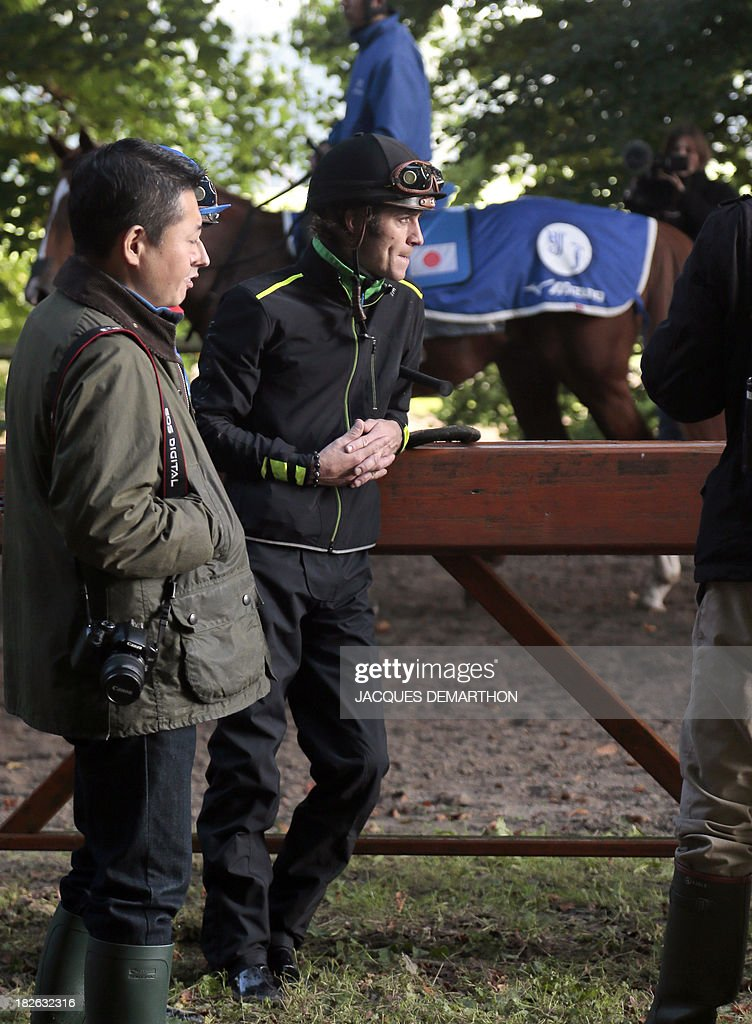 Belgian jockey Christophe Soumillon (C) attends a debriefing after a training session as a lad rides Orfevre (back) in Chantilly, north of Paris, on October 2, 2013 ahead of the Qatar Prix de l'Arc de Triomphe on October 6, 2013. AFP PHOTO / JACQUES DEMARTHON