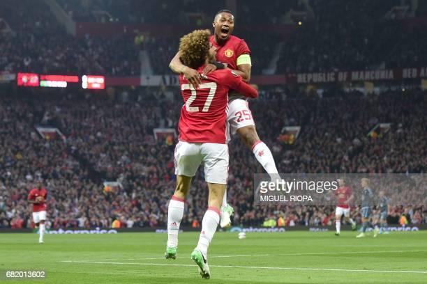 Belgian midfielder Marouane Fellaini celebrates with Manchester United's Ecuadorian midfielder Antonio Valencia after scoring the opening goal of the...