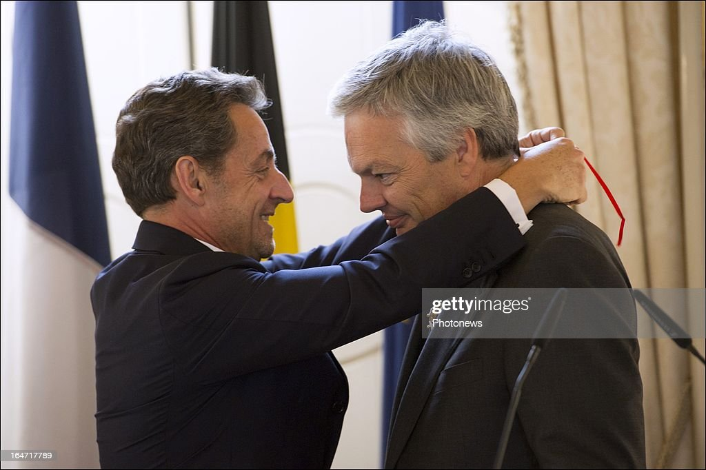 Belgian Minister of Foreign Affairs Didier Reynders receives the Legion d'Honneur from former French president Nicolas Sarkozy on March 27, 2013 in Brussels, Belgium.