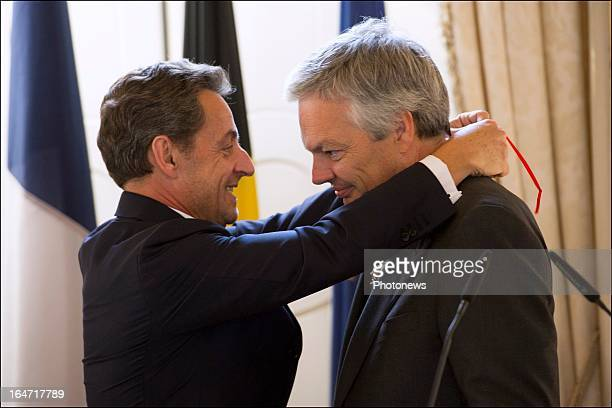 Belgian Minister of Foreign Affairs Didier Reynders receives the Legion d'Honneur from former French president Nicolas Sarkozy on March 27 2013 in...