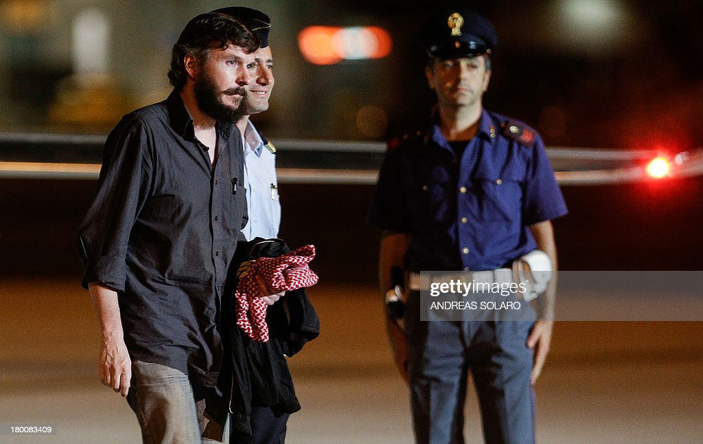 Belgian national Pierre Piccinin (L) and Italian journalist Domenico Quirico (unseen), both kidnapped in Syria in early April, disembark from the airplane on September 9, 2013 at Ciampino military airport in Rome. AFP PHOTO / ANDREAS SOLARO