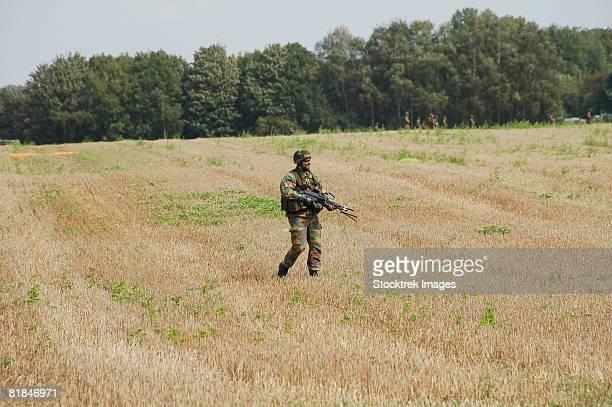 Belgian paratroopers proceeding in the fields.