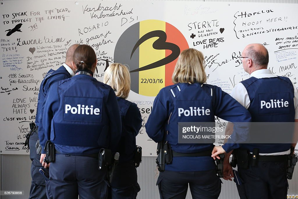 Belgian police forces read messages on a commemorative wall on May 1, 2016 at Zaventem airport in Brussels during the opening ceremony of the departure hall, closed since the March 22 attacks. Brussels airport was hit on March 22, 2016 by one of the three Islamic State suicide bombers who struck the airport and Maelbeek - Maalbeek metro station on March 22, killing 32 people and injuring hundreds. / AFP / Belga / NICOLAS MAETERLINCK / Belgium OUT