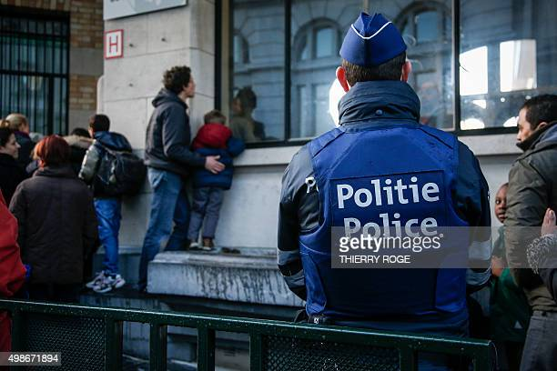 A Belgian police officer watches parents waiting as he patrols outside the Athenee Robert Catteau School on November 25 in Brussels Schools and some...
