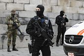 Belgian police officers and soldiers stand guard outside the Brussels Palace of Justice during the appearance before the council chamber of two...