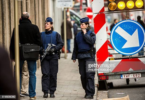 Belgian police officers patrol near Maalbeek Maelbeek metro station in Brussels on March 22 2016 after a series of apparently coordinated explosions...