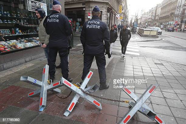 Belgian police officers stand guard as people gather in the Place de la Bourse to pay tribute to the 31 victims of the attacks in Brussels last week...