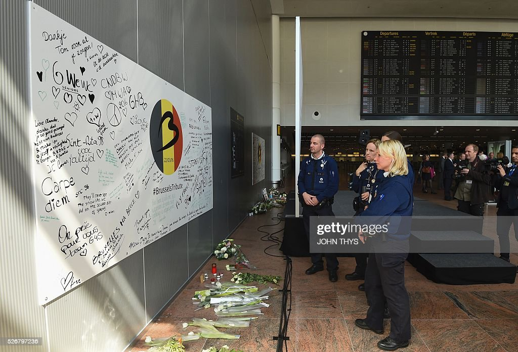 Belgian police officers stand in front of a wall with signatures of airport workers during the partial reopening of the departure hall of Brussels Airport in Zaventem on May 1, 2016, after it was badly damaged in twin suicide attacks on March 22, that killed 16 people. A total of 32 people were killed and more than 300 wounded in coordinated suicide bombings at the airport and a metro station in central Brussels on March 22 in Belgium's worst ever terror attacks. / AFP / JOHN