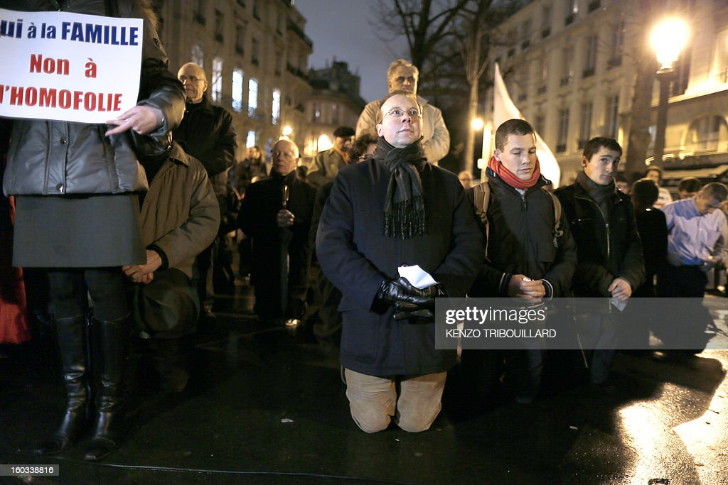 Belgian president of the French fundamentalist Christians group Civitas, Alain Escada (C), prays during a protest against same-sex marriage on January 29, 2013 in Paris. France's parliament began today examining draft legislation on same-sex marriage after months of rancorous debate and huge street protests by both supporters and opponents. At left, the board reads : 'Yes for the family, no to the homophoby'.