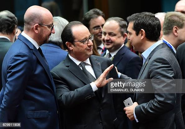 Belgian Prime Minister Charles Michel looks at French President Francois Hollande and Greek Prime Minister Alexis Tsipras talking during an European...