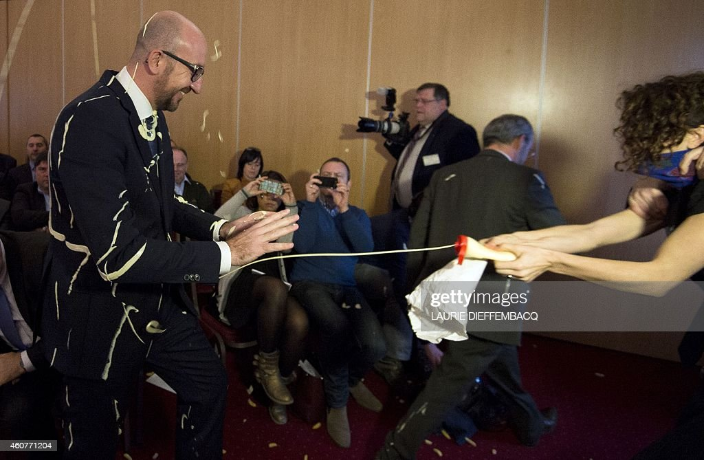 Belgian Prime Minister <a gi-track='captionPersonalityLinkClicked' href=/galleries/search?phrase=Charles+Michel+-+Politician&family=editorial&specificpeople=13722663 ng-click='$event.stopPropagation()'>Charles Michel</a> (L) reacts as activists throw fries and mayonnaise on him during an anti-government protest by feminist activist group LilithS (formerly the Belgian branch of Femen) at a press conference at the Cercle de Wallonie in Namur on December 22, 2014. AFP PHOTO / BELGA / LAURIE DIEFFEMBACQ == BELGIUM OUT ==