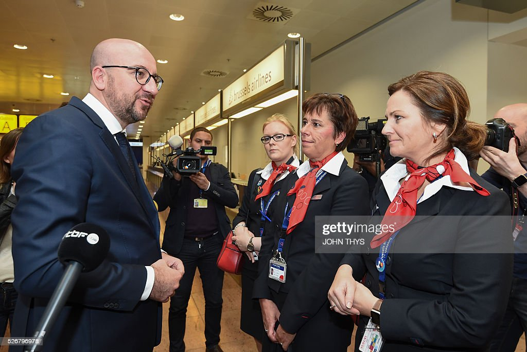 Belgian Prime Minister Charles Michel speaks with airport personnel during the partial reopening of the departure hall of Brussels Airport in Zaventem on May 1, 2016, after it was badly damaged in twin suicide attacks on March 22, that killed 16 people. A total of 32 people were killed and more than 300 wounded in coordinated suicide bombings at the airport and a metro station in central Brussels on March 22 in Belgium's worst ever terror attacks. / AFP / JOHN