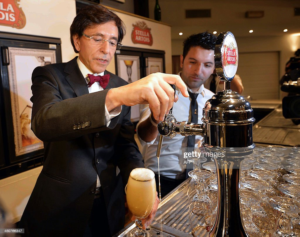 Belgian Prime Minister Elio Di Rupo pours beer into a glass during a visit to AB Inbev's Stella Artois brewery in Leuven on November 20, 2013.