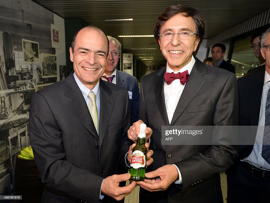 Belgian Prime Minister Elio Di Rupo (R) receives the 600 millionth bottle from Carlos Brito, CEO of AB Inbev during a visit of AB Inbev brewery Stella Artois, in Leuven, on November 20, 2013.
