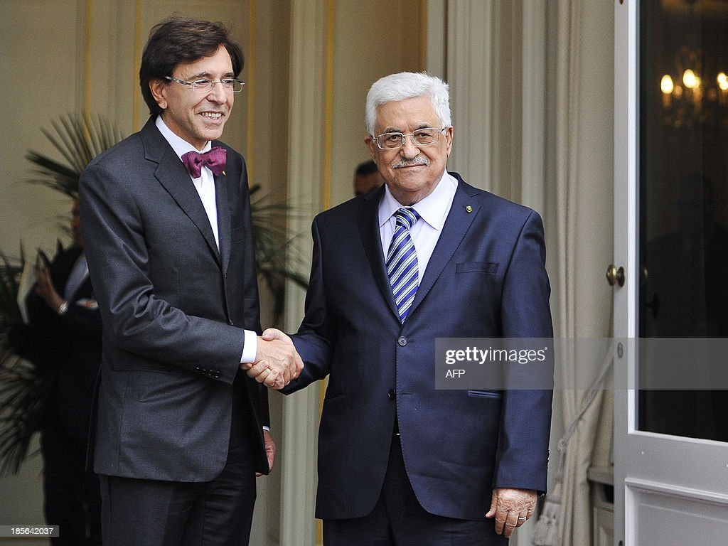 Belgian Prime Minister Elio Di Rupo (L) shakes hands with Palestinian president Mahmud Abbas on October 23, 2013 during a bilateral meeting at the Lambermont Residence of the Belgian prime minister in Brussels. OUT -