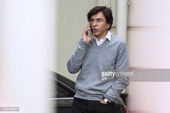 Belgian Prime Minister Elio Di Rupo talks on a cell phone as ministers arrive for a kern meeting a restricted ministers budget meeting at the Prime...