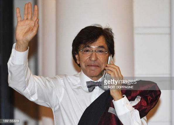 Belgian Prime Minister Elio Di Rupo waves and speaks on the phone as he arrives for a kern restricted ministers meeting in Brussels on January 9 2013...