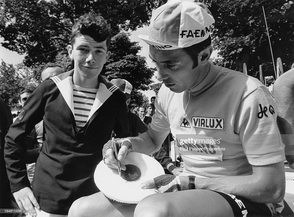 Belgian racing cyclist <a gi-track='captionPersonalityLinkClicked' href=/galleries/search?phrase=Eddy+Merckx&family=editorial&specificpeople=213957 ng-click='$event.stopPropagation()'>Eddy Merckx</a> autographs a sailor's cap during the Tour de France, 28th June 1970. Merckx went on to win the tour.