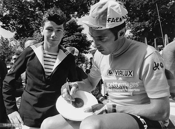 Belgian racing cyclist Eddy Merckx autographs a sailor's cap during the Tour de France 28th June 1970 Merckx went on to win the tour