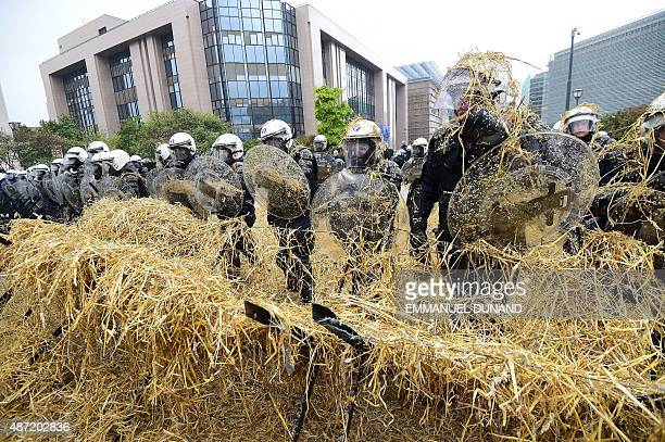 Belgian riot police stand covered in straw sprayed from a combine harvester by European farmers during a protest blocking access to the European...