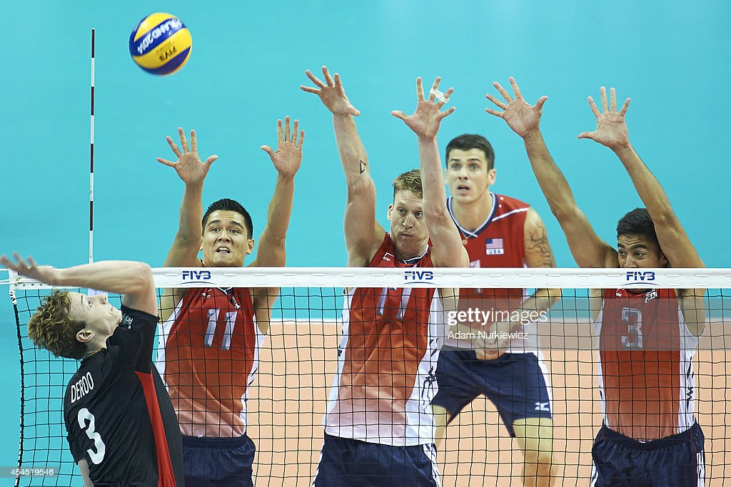 Belgian Sam Deroo (left) attacks against Micah Christenson and Maxwell Holt and Taylor Sander of USA during the FIVB World Championships Volleyball at Cracow Arena on August 31, 2014 in Cracow, Poland.