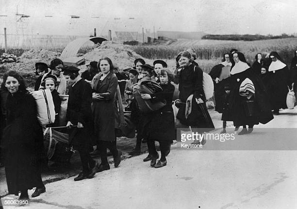 Belgian schoolgirls and nuns displaced from their convent by German attacks on the Low Countries arrive at a French refugee centre during World War...