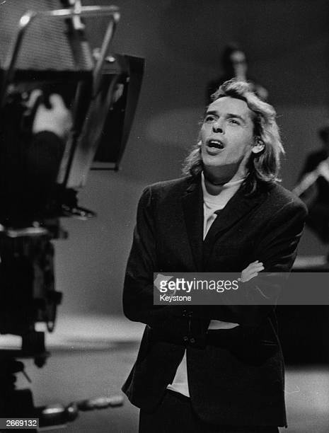 Belgian singer and poet Jaques Brel records for his French television series 'Do You Like Music '