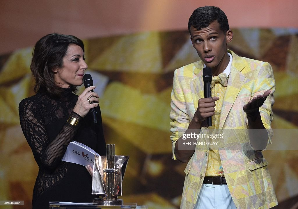 Belgian singer Paul Van Haver (R), aka Stromae, delivers a speech next to French TV host Virginie Guilhaume (L) after receiving the men's artist of the year award during the 29th Victoires de la Musique, the annual French music awards ceremony, on February 14, 2014 at the Zenith concert hall in Paris. AFP PHOTO / BERTRAND GUAY