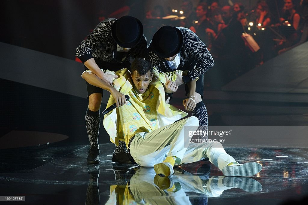 Belgian singer Paul Van Haver (C), aka Stromae, performs on stage during the 29th Victoires de la Musique, the annual French music awards ceremony, on February 14, 2014 at the Zenith concert hall in Paris. AFP PHOTO / BERTRAND GUAY
