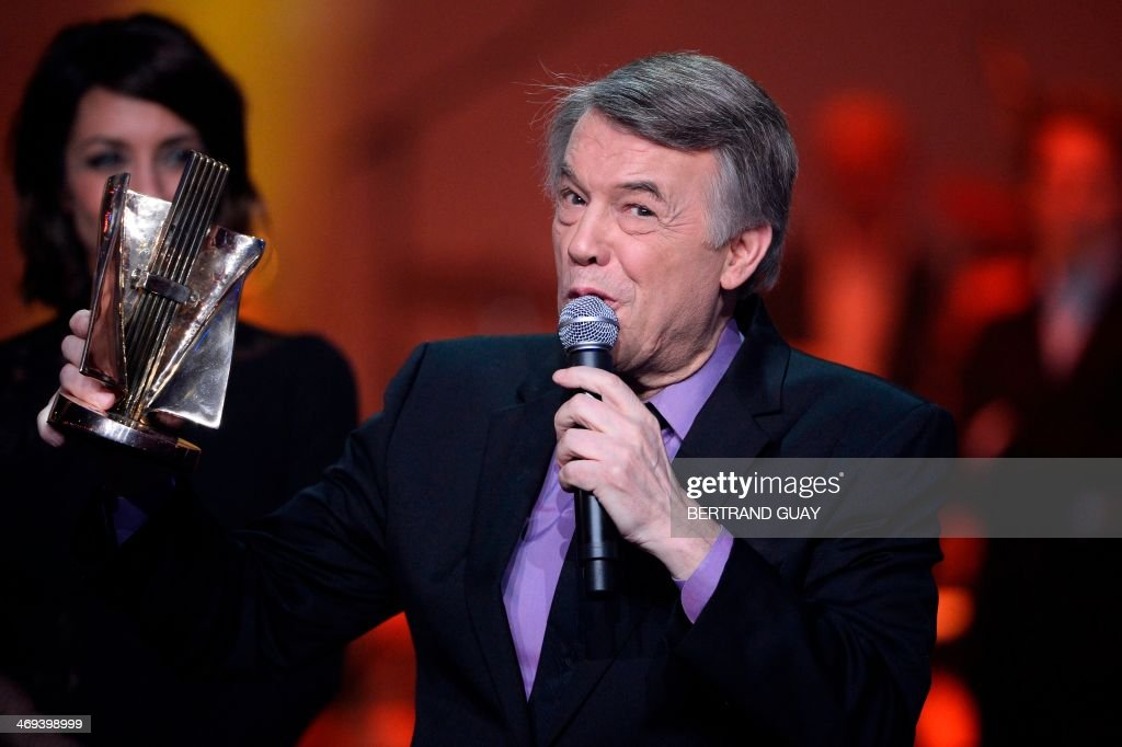 Belgian singer Salvatore Adamo delivers a speech after receiving an honorary award for his life time achievement during the 29th Victoires de la Musique, the annual French music awards ceremony, on February 14, 2014 at the Zenith concert hall in Paris. AFP PHOTO / BERTRAND GUAY