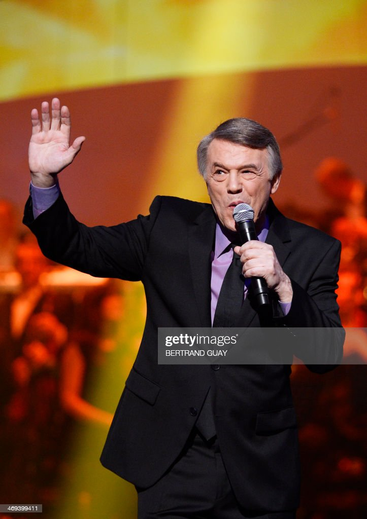 Belgian singer Salvatore Adamo waves as he performs during the 29th Victoires de la Musique, the annual French music awards ceremony, on February 14, 2014 at the Zenith concert hall in Paris.