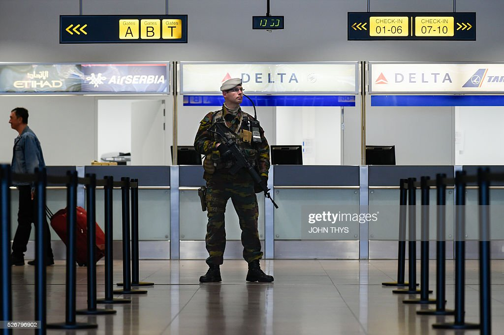 A Belgian soldier stands guard in front of the desk of US airline Delta Air Lines during the partial reopening of the departure hall of Brussels Airport in Zaventem on May 1, 2016, after it was badly damaged in twin suicide attacks on March 22, that killed 16 people. A total of 32 people were killed and more than 300 wounded in coordinated suicide bombings at the airport and a metro station in central Brussels on March 22 in Belgium's worst ever terror attacks. / AFP / JOHN