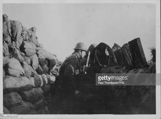 A Belgian soldier watching for signs of enemy movement from behind sandbags France circa 19141918