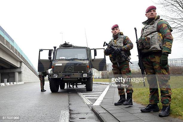 Belgian soldiers stand guard outside of the closed Brussels Zaventem airport on March 23 2016 in Brussels Belgium Belgium is observing three days of...