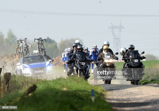 Belgian Tom Boonen of QuickStep Floors followed by the team cycles behind motos on April 7 2017 in Orchies during a training ahead of the...