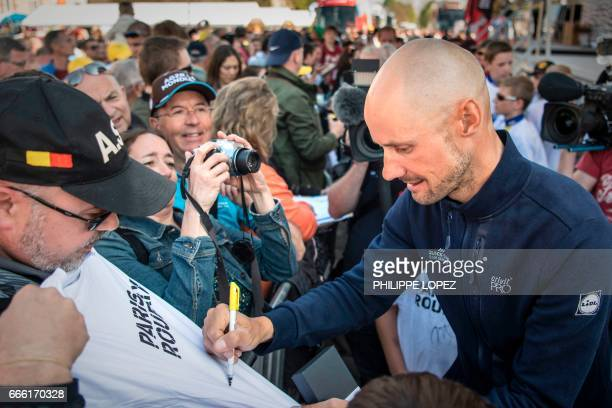 Belgian Tom Boonen of QuickStep Floors signs a Tshirt for a fan after the team presentation n April 8 2017 on the eve of the ParisRoubaix cycling...
