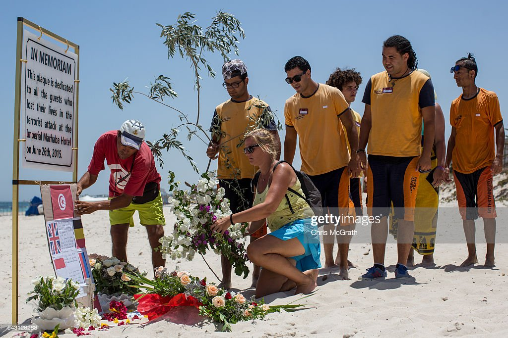 A Belgian tourist, joined by local hotel staff place flowers at a memorial sign on the beach in front of the Imperial Marhaba hotel on June 26, 2016 in Sousse, Tunisia. Today marks the one year anniversary of the Sousse Beach terrorist attack, which killed 38 people including 30 Britons. Before the 2011 revolution, tourism in Tunisia accounted for approximately 7% of the country's GDP. The two 2015 terrorist attacks at the Bardo Museum and Sousse Beach saw tourism numbers plummet even further forcing hotels to close and many tourism and hospitality workers to lose their jobs.