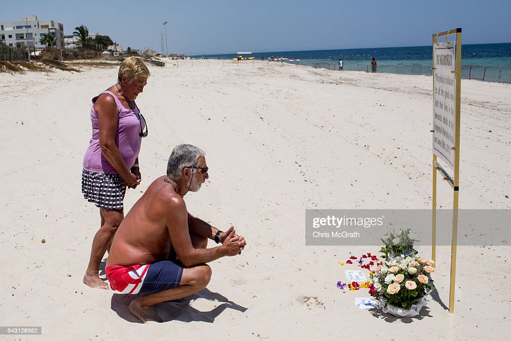 Belgian tourists take a moment to remember the victims of the 2015 Sousse Beach terrorist attack at a memorial sign on the beach in front of the Imperial Marhaba hotel on June 26, 2016 in Sousse, Tunisia. Today marks the one year anniversary of the Sousse Beach terrorist attack, which killed 38 people including 30 Britons. Before the 2011 revolution, tourism in Tunisia accounted for approximately 7% of the country's GDP. The two 2015 terrorist attacks at the Bardo Museum and Sousse Beach saw tourism numbers plummet even further forcing hotels to close and many tourism and hospitality workers to lose their jobs.
