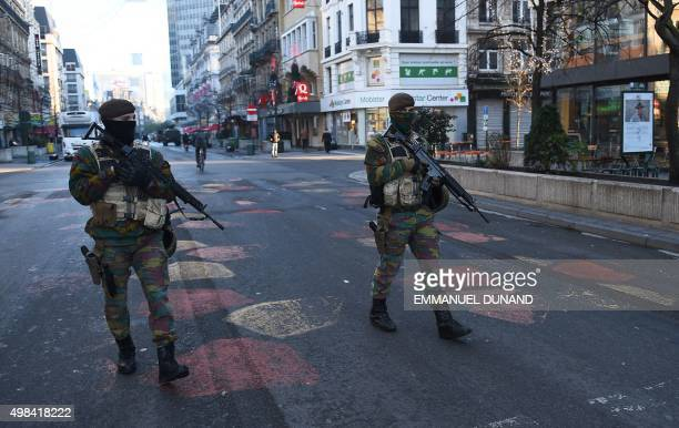 Belgian troops patrol a street in Brussels on November 23 2015 as the Belgian capital remains on the highest possible alert level Brussels began a...