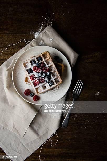 Belgian waffles with blueberries, raspberries and icing sugar dusting