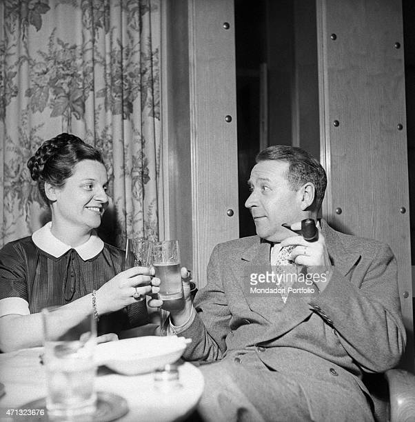 Belgian writer Georges Simenon and his wife Denyse Ouimet toasting Milan 1957