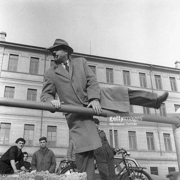Belgian writer Georges Simenon jumping over a railing Milan 1957
